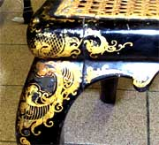 Close-up of gold decoration on top of leg